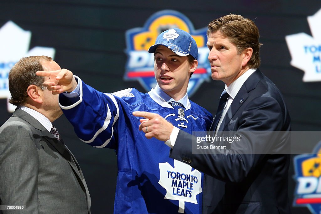 Head coach Mike Babcock of the Toronto Maple Leafs talks with Mitchell Marner after being selected fourth overall by the Toronto Maple Leafs in the first round of the 2015 NHL Draft at BB&T Center on June 26, 2015 in Sunrise, Florida.