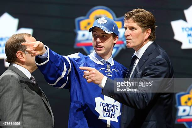 Head coach Mike Babcock of the Toronto Maple Leafs talks with Mitchell Marner after being selected fourth overall by the Toronto Maple Leafs in the...