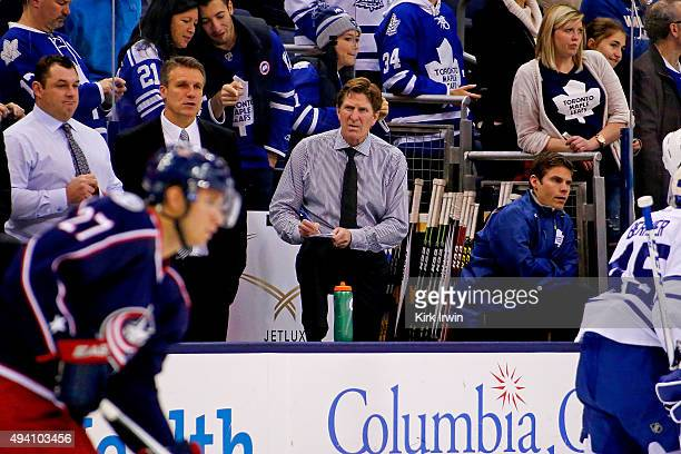 Head Coach Mike Babcock of the Toronto Maple Leafs watches as the Columbus Blue Jackets warm up prior to the start of the game between the Columbus...