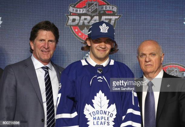 Head coach Mike Babcock Timothy Liljegren 17th overall pick of the Toronto Maple Leafs and general manager Lou Lamoriello pose for a photo onstage...