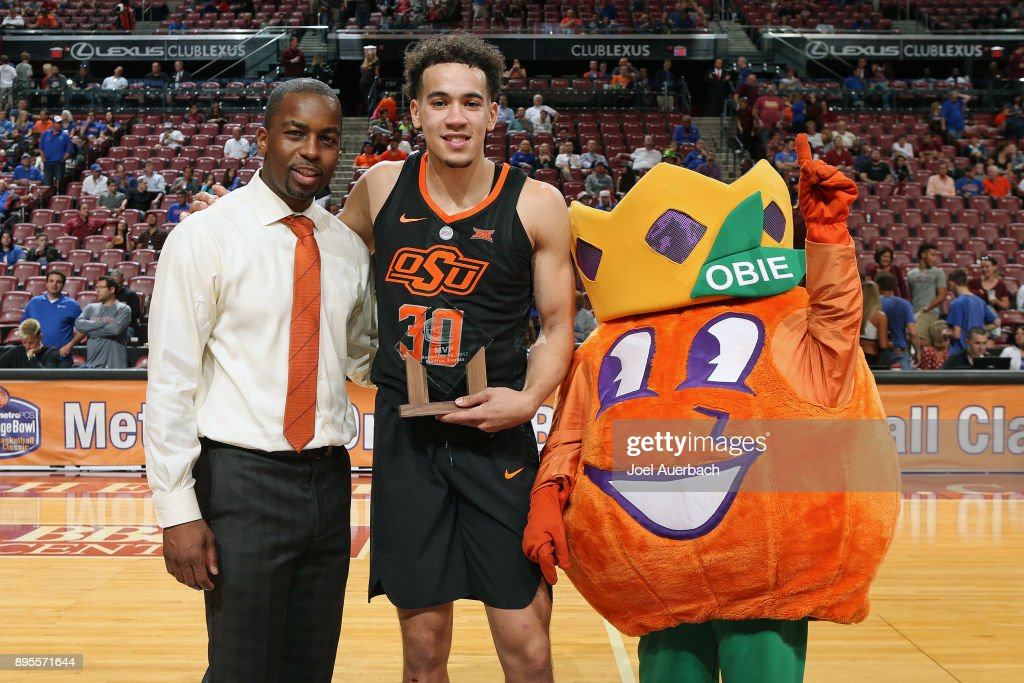 Head coach Mike Boynton poses with Jeffrey Carroll #30 of the Oklahoma State Cowboys and Obie, the Orange Bowl mascot after Carroll is awarded the MVP trophy after the game against the Florida State Seminoles during the MetroPCS Orange Bowl Basketball Classic on December 16, 2017 at the BB&T Center in Sunrise, Florida. Oklahoma State defeated Florida State 71-70.
