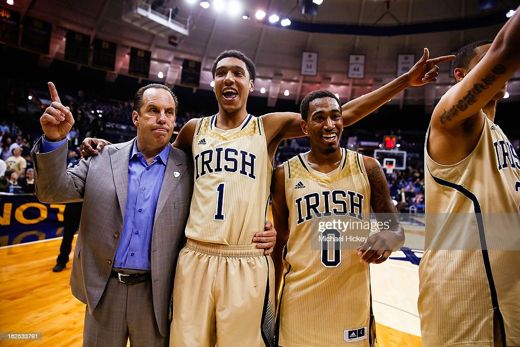 Head coach <a gi-track='captionPersonalityLinkClicked' href=/galleries/search?phrase=Mike+Brey&family=editorial&specificpeople=221188 ng-click='$event.stopPropagation()'>Mike Brey</a> of the Notre Dame Fighting Irish, Cameron Biedscheid #1 of the Notre Dame Fighting Irish and <a gi-track='captionPersonalityLinkClicked' href=/galleries/search?phrase=Eric+Atkins&family=editorial&specificpeople=7379862 ng-click='$event.stopPropagation()'>Eric Atkins</a> #0 of the Notre Dame Fighting Irish sing the Alma Mater following their win over the Cincinnati Bearcats at Purcel Pavilion on February 24, 2013 in South Bend, Indiana. Notre Dame defeated Cincinnati 62-41.