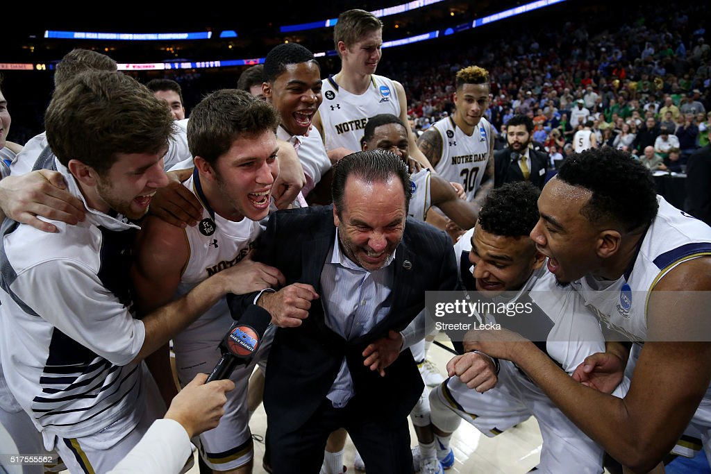 Head coach <a gi-track='captionPersonalityLinkClicked' href=/galleries/search?phrase=Mike+Brey&family=editorial&specificpeople=221188 ng-click='$event.stopPropagation()'>Mike Brey</a> of the Notre Dame Fighting Irish celebrates with his team after defeating the Wisconsin Badgers with a score of 56 to 61 during the 2016 NCAA Men's Basketball Tournament East Regional at Wells Fargo Center on March 25, 2016 in Philadelphia, Pennsylvania.