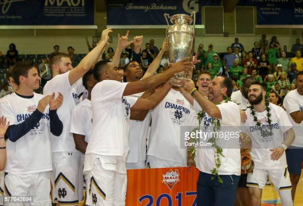 Head coach Mike Brey of the Notre Dame Fighting Irish hands over the Championship Trophy to his players after winning the 2107 Maui Invitational at...