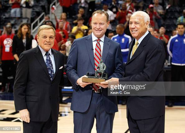 Head coach Mike Budenholzer of the Atlanta Hawks accepts the 201415 NBA Coach of the Year Award from former Atlanta Hawks head coaches Mike Fratello...