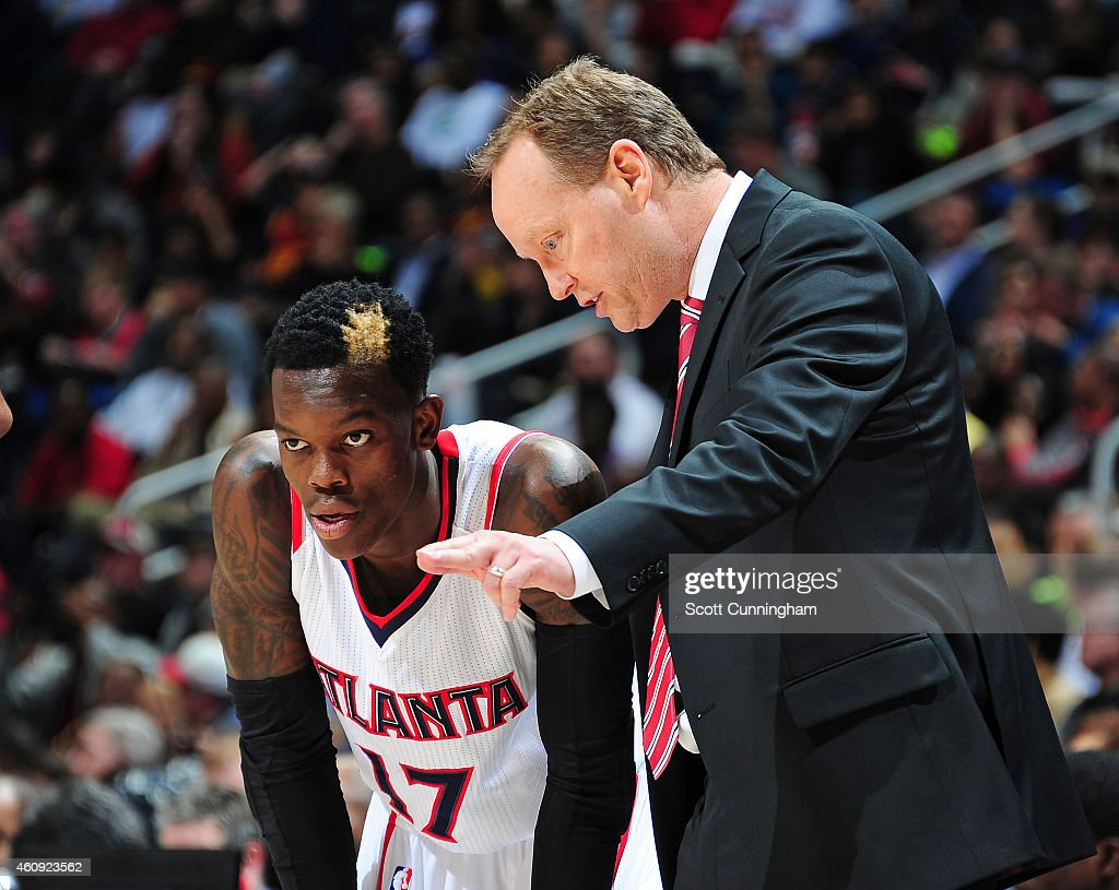 Head Coach Mike Budenholzer of the Atlanta Hawks discusses a play with Dennis Schroder during the game against the Cleveland Cavaliers on December 30...