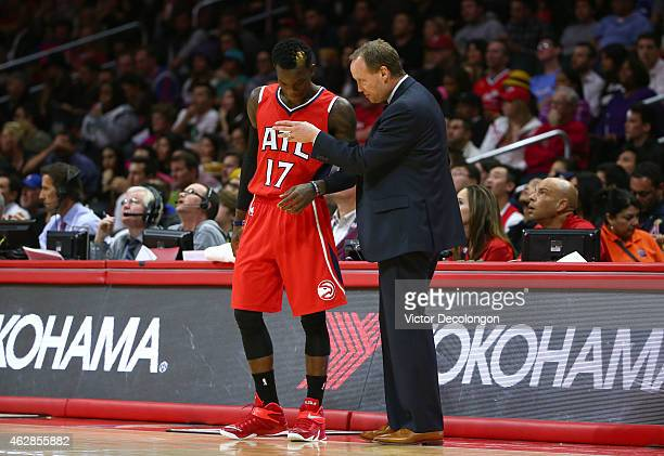 Head Coach Mike Budenholzer of the Atlanta Hawks speaks to Dennis Schroder of the Atlanta Hawks on the side line during the NBA game against the Los...