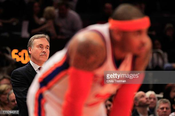 Head coach Mike D'Antoni looks on over his player Carmelo Anthony of the New York Knicks during the game against the New Jersey Nets at Madison...