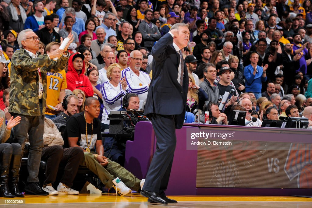 Head Coach Mike D'Antoni of the Los Angeles Lakers cheers his team on against the Oklahoma City Thunder as recording artist Jay-Z looks on behind him at Staples Center on January 27, 2013 in Los Angeles, California.