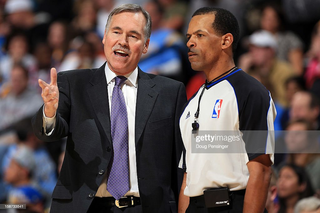 Head coach Mike D'Antoni of the Los Angeles Lakers protests a call with referee referee Eric Lewis against the Denver Nuggets at Pepsi Center on...