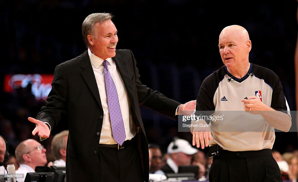Head coach Mike D'Antoni of the Los Angeles Lakers smiles as he argues a call with referee Joe Crawford during the game with the Detroit Pistons at Staples Center on November 17, 2013 in Los Angeles, California. The Lakers won 114-99.