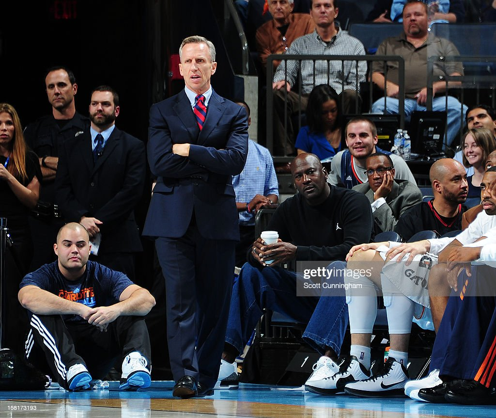 Head Coach <a gi-track='captionPersonalityLinkClicked' href=/galleries/search?phrase=Mike+Dunlap&family=editorial&specificpeople=3957174 ng-click='$event.stopPropagation()'>Mike Dunlap</a> of the Charlotte Bobcats looks on as the team's owner, <a gi-track='captionPersonalityLinkClicked' href=/galleries/search?phrase=Michael+Jordan+-+Basketball+Player&family=editorial&specificpeople=73625 ng-click='$event.stopPropagation()'>Michael Jordan</a>, sits behind him during a game against the Golden State Warriors at Time Warner Cable Arena on December 10, 2012 in Charlotte, North Carolina.