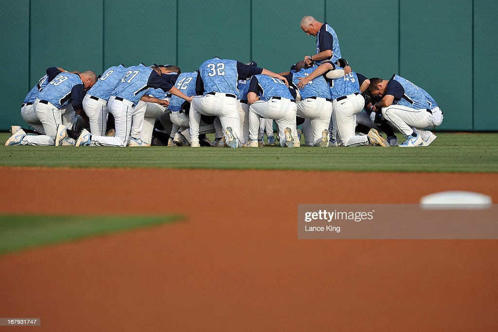 Head Coach Mike Fox (standing) of the North Carolina Tar Heels prays with his team prior to a game against the North Carolina State Wolfpack at Doak Field on April 26, 2013 in Raleigh, North Carolina. North Carolina defeated NC State 7-1.