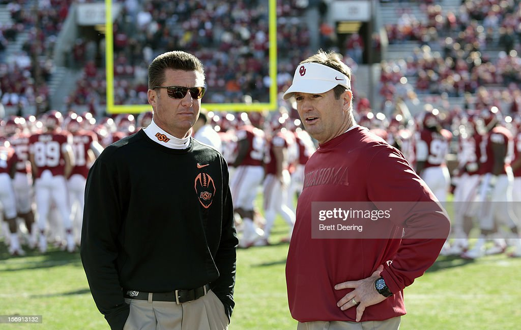 Head Coach Mike Gundy of the Oklahoma State Cowboys and Head Coach <a gi-track='captionPersonalityLinkClicked' href=/galleries/search?phrase=Bob+Stoops&family=editorial&specificpeople=241307 ng-click='$event.stopPropagation()'>Bob Stoops</a> of the Oklahoma Sooners meet before the game November 24, 2012 at Gaylord Family-Oklahoma Memorial Stadium in Norman, Oklahoma. Oklahoma defeated Oklahoma State 51-48 in overtime.