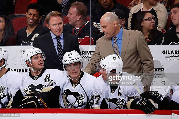 Head coach Mike Johnston and assistant coach Rick Tocchet of the Pittsburgh Penguins talk with players on the bench during the second period of the...