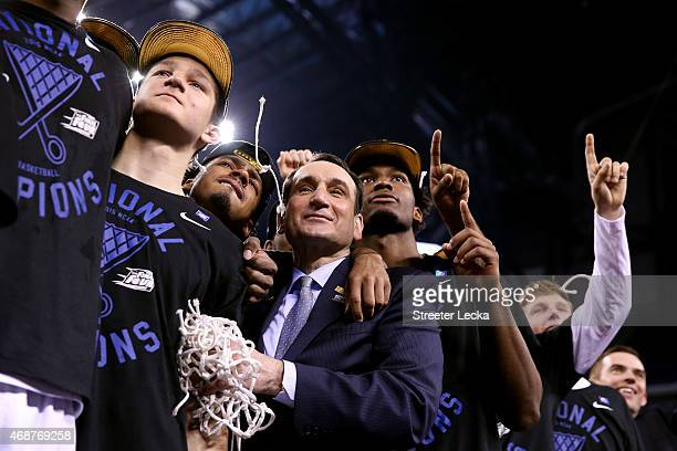 Head coach Mike Krzyzewski of the Duke Blue Devils watches 'One Shining Moment' with his players Grayson Allen Quinn Cook and Justise Winslow after...