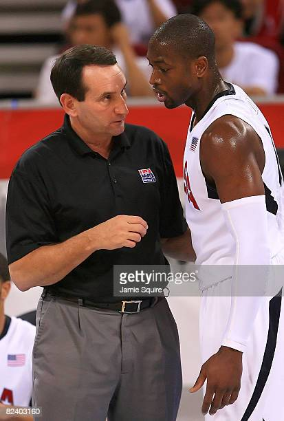 Head coach Mike Krzyzewski of the United States speaks with Dwyane Wade on the sidelines during the mens basketball preliminaries against Germany at...
