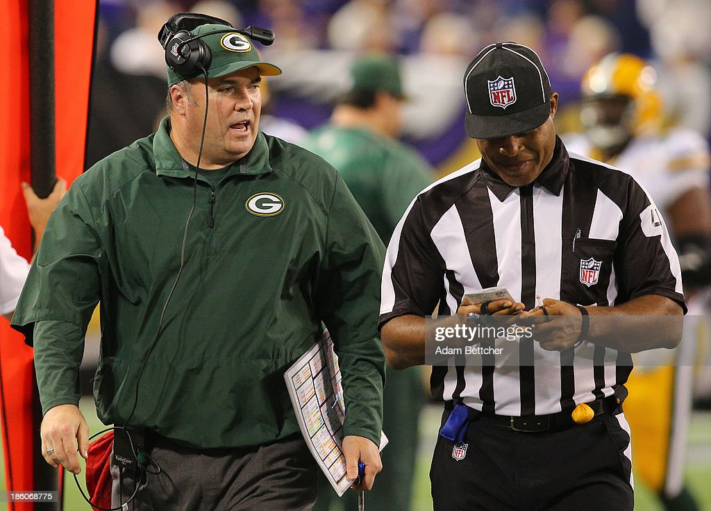 Head coach Mike McCarthy of the Green Bay Packers chats up a referee during the game against the Minnesota Vikings on October 27, 2013 at Mall of America Field at the Hubert Humphrey Metrodome in Minneapolis, Minnesota.