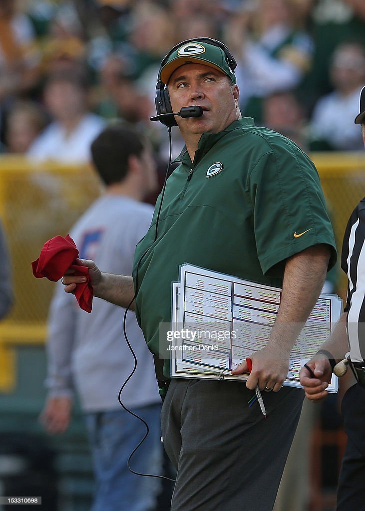 Head coach Mike McCarthy of the Green Bay Packers looks at the replay board as he holds the challenge flag against the New Orleans Saints at Lambeau Field on September 30, 2012 in Green Bay, Wisconsin. The Packers defeated the Saints 28-27.