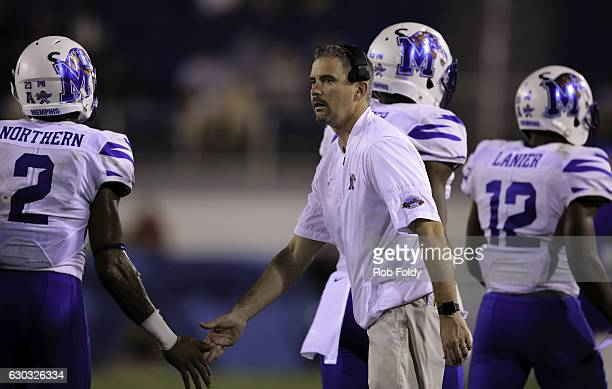 Head coach Mike Norvell of the Memphis Tigers slaps hands with players during the fourth quarter of the game against the Western Kentucky Hilltoppers...