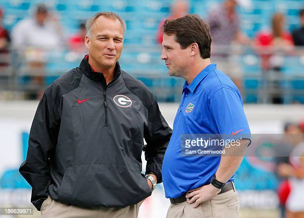 Head coach Mike Richt of the Georgia Bulldogs speaks with head coach Will Muschamp of the Florida Gators before the game at EverBank Field on...