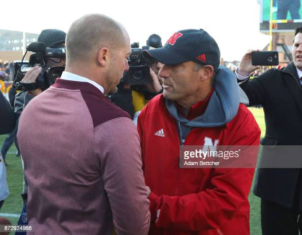 Head coach Mike Riley of the Nebraska Cornhuskers and head coach PJ Fleck of the Minnesota Golden Gophers greet on the field after the game at TCF...