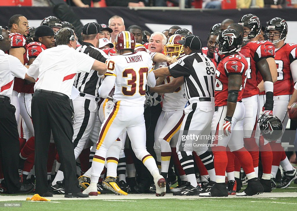 Head Coach Mike Smith of the Atlanta Falcons scuffles with LaRon Landry and DeAngelo Hall of the Washington Redskins at the Georgia Dome on November...
