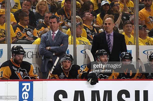 Head Coach Mike Sullivan and assistant coach Rick Tocchet of the Pittsburgh Penguins look on from behind the bench during the third period of Game...