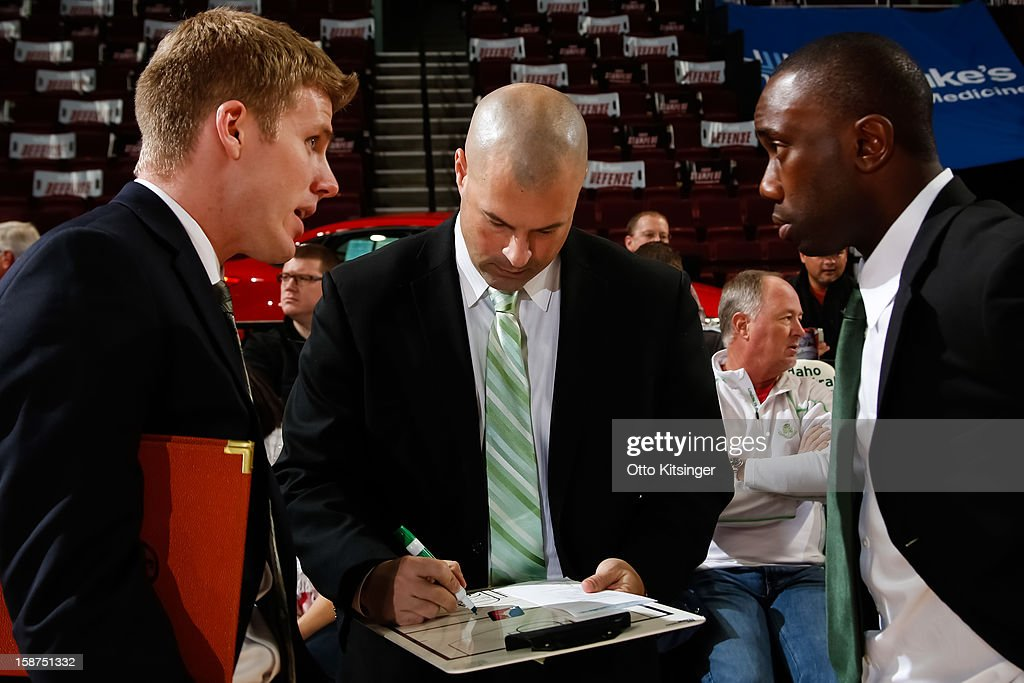 Head Coach Mike Taylor of the Maine Red Claws writes while Assistant Coaches J.P. Clark and Tunde Adekola talk during the NBA D-League game against the Idaho Stampede on December 26, 2012 at CenturyLink Arena in Boise, Idaho.