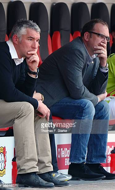 Head coach Mirko Slomka and manager Joerg Schmadtke of Hannover sit dejected on the substitutes bench during the Bundesliga match between Bayer...