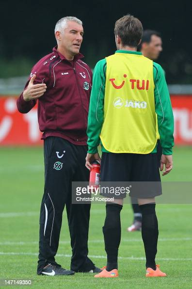 Head coach Mirko Slomka speaks to Adrian Nikci during the training session of Hannover 96 at Mehrkampfanlage on June 26 2012 in Hanover Germany