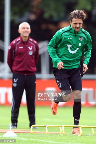 Head coach Mirko Slomka watches Adrian Nikci running during the training session of Hannover 96 at Mehrkampfanlage on June 26 2012 in Hanover Germany
