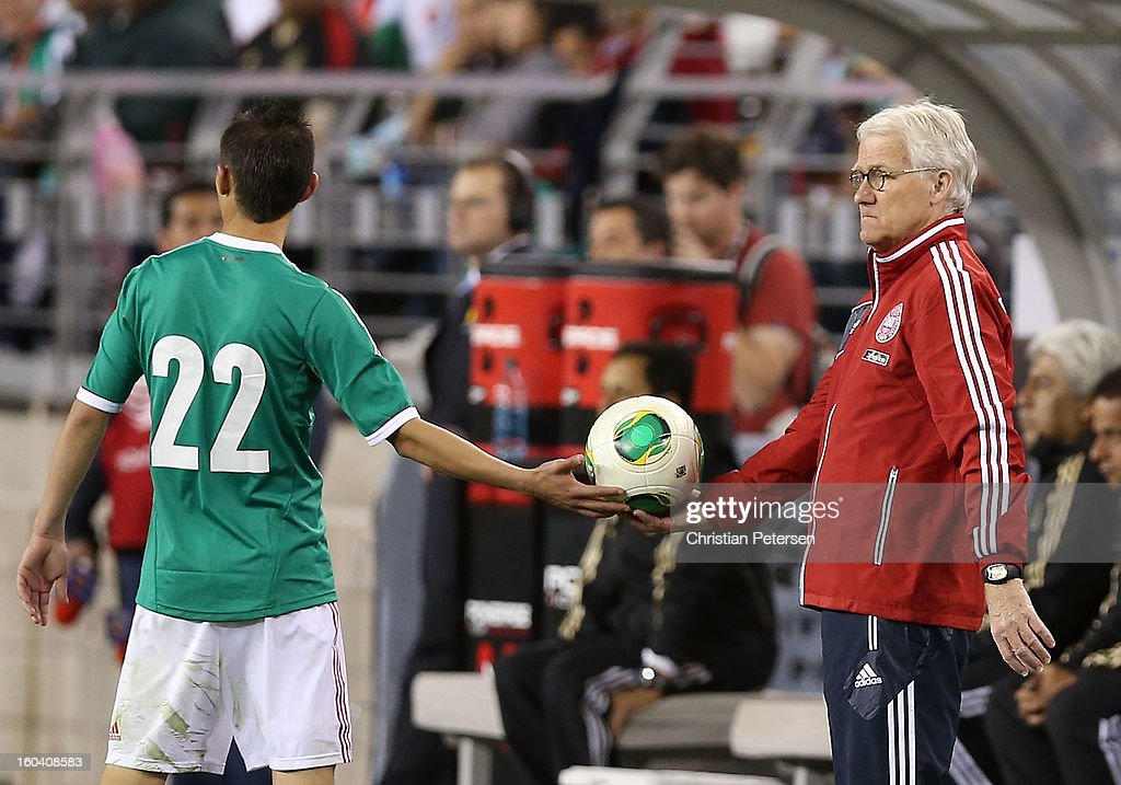 Head coach <a gi-track='captionPersonalityLinkClicked' href=/galleries/search?phrase=Morten+Olsen&family=editorial&specificpeople=687278 ng-click='$event.stopPropagation()'>Morten Olsen</a> of Denmark hands the ball to <a gi-track='captionPersonalityLinkClicked' href=/galleries/search?phrase=Paul+Aguilar&family=editorial&specificpeople=4476672 ng-click='$event.stopPropagation()'>Paul Aguilar</a> #22 of Mexico during an international friendly match at University of Phoenix Stadium on January 30, 2013 in Glendale, Arizona. Mexico and Denmark ended in a 1-1 draw.