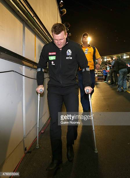 head coach Nathan Buckley of the Magpies heads down the race on crutchers during the round 10 AFL match between the Melbourne Demons and the...