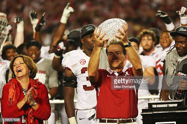 Head coach Nick Saban of the Alabama Crimson Tide celebrates with the BCS Coaches' Trophy as his wife Terry looks on after defeating the Notre Dame...