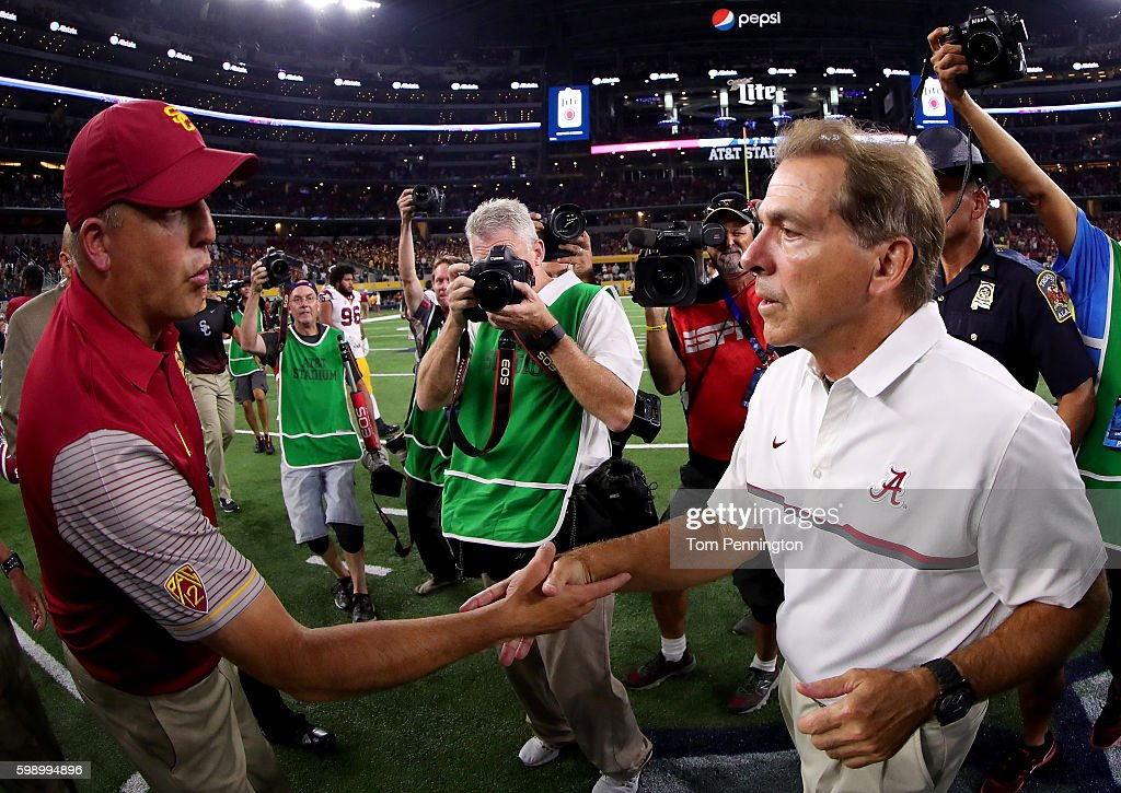head coach Nick Saben of the Alabama Crimson Tide greets head coach Clay Helton of the USC Trojans at midfield after the Alabama Crimson Tide beat the USC Trojans 52-6 during the AdvoCare Classic at AT&T Stadium on September 3, 2016 in Arlington, Texas.
