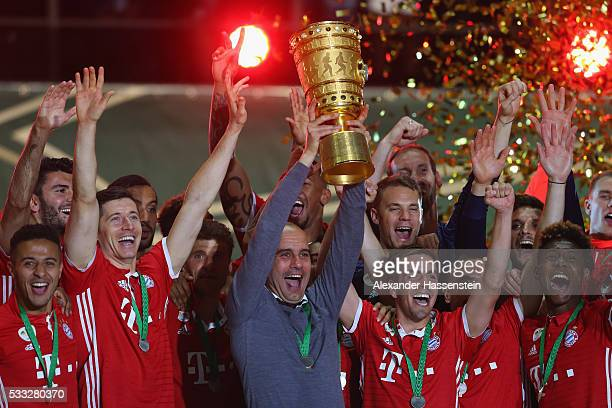 Head coach of Bayern Muenchen Pep Guardiola lifts the trophy with his team to celebrate victory after the DFB Cup Final match between Bayern Muenchen...
