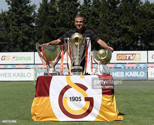 Head coach of Galatasaray Hamza Hamzaoglu poses with the 20142015 Turkish Cup Turkish Spor Toto Super League and Turkish Super Cup trophies in...