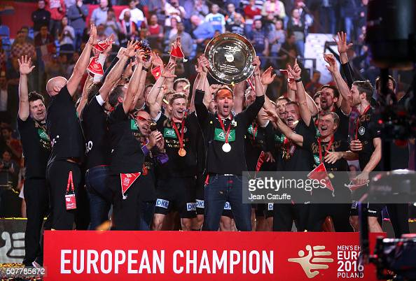 Head coach of Germany Dagur Sigurdsson holds the trophy while his players celebrate the victory during the trophy ceremony following the final of the...