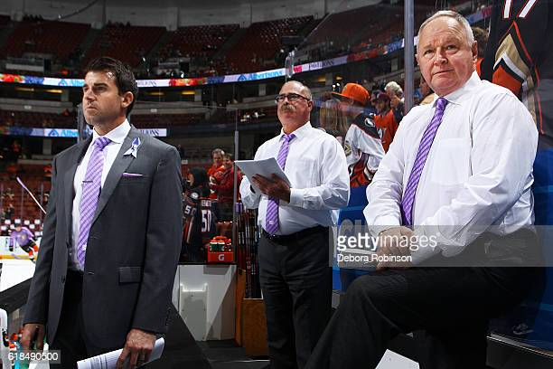 Head coach of the Anaheim Ducks Randy Carlyle right and Assistant Coaches Paul MacLean center and Joe Piscotty watch from the bench during warmups...