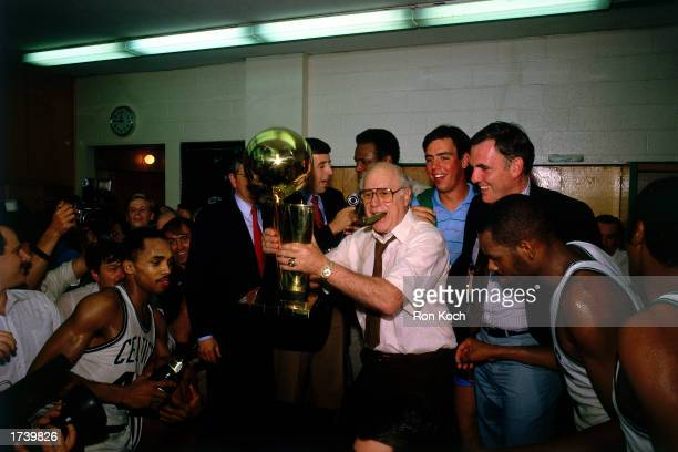Head coach of the Boston Celtics Red Auerbach holds the NBA Championship Trophy after winning the 1984 NBA Championship at the Boston Garden on June...