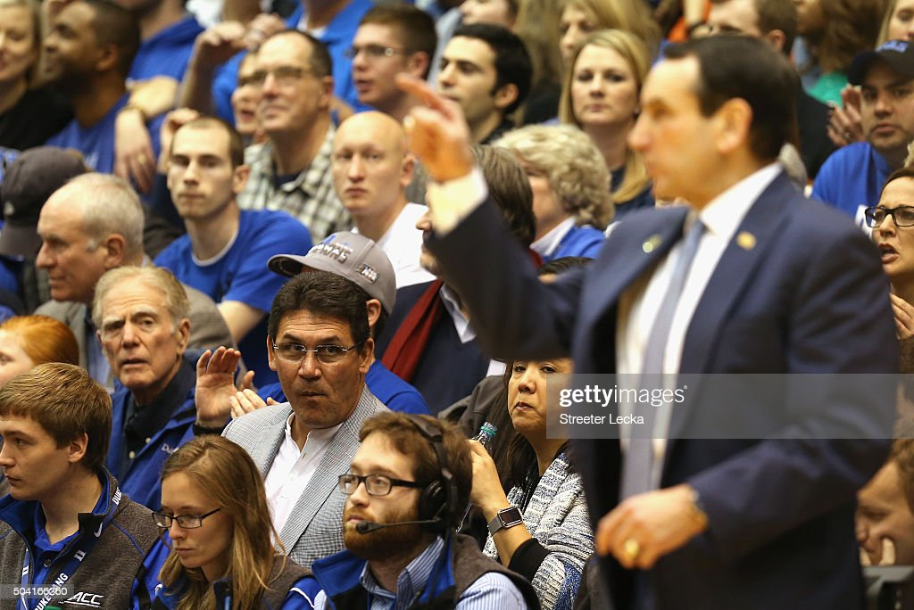 Head coach of the Carolina Panthers Ron Rivera watches head coach Mike Krzyzewski of the Duke Blue Devils during the game between the Virginia Tech...