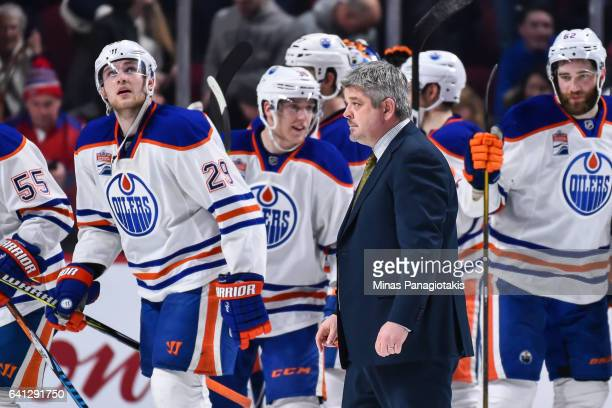 Head coach of the Edmonton Oilers Todd McLellan walks past his team as they celebrate a victory over the Montreal Canadiens during the NHL game at...
