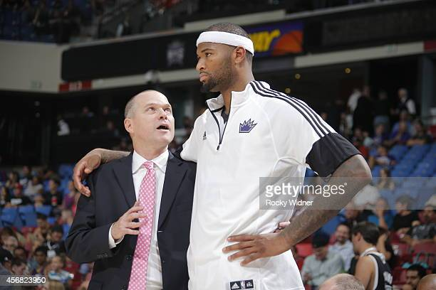 Head Coach of the Sacramento Kings Michael Malone speaks to DeMarcus Cousins during a game against the Toronto Raptors at the Sleep Train Arena in...