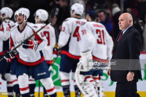 Head coach of the Washington Capitals Barry Trotz walks by his team as they celebrate a victory during the NHL game against the Montreal Canadiens at...