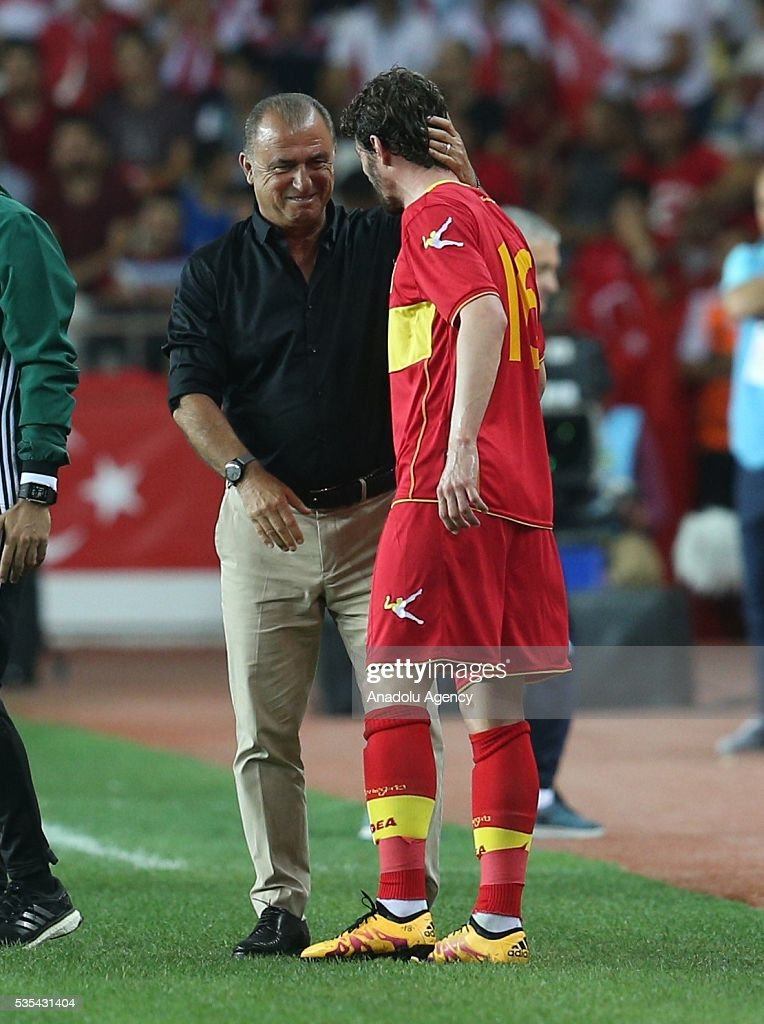 Head coach of Turkey's national football team Fatih Terim celebrate Kascelan (R) of Montenegro at his jubilee as Kascelan leaves the match during the friendly football match between Turkey and Montenegro at Antalya Ataturk Stadium in Antalya, Turkey on May 29, 2016.