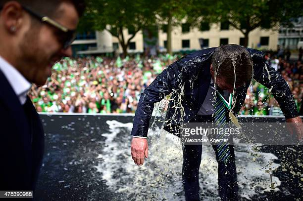 Head Coach of VfL Wolfsburg DIeter Hecking reacts after being shower with beer by team mates while on stage at Rathausplatz to celebrate the winning...