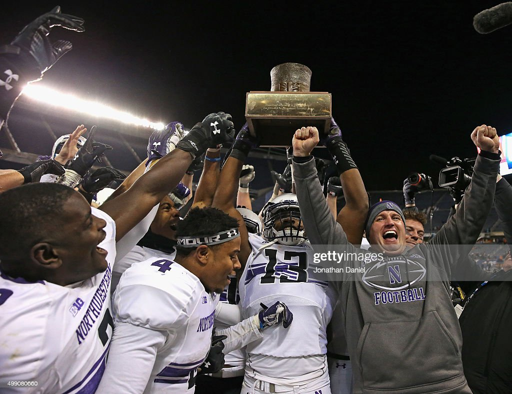 Head coach <a gi-track='captionPersonalityLinkClicked' href=/galleries/search?phrase=Pat+Fitzgerald&family=editorial&specificpeople=877167 ng-click='$event.stopPropagation()'>Pat Fitzgerald</a> of the Northwestern Wildcats (R) celebrates with his team including (L-R) Traveon Henry #2, Solomon Vault #4 and Deonte Gibson #13 as they hold the 'Land of Lincoln' trophy after a win over the Illinois Fighting Illini at Soldier Field on November 28, 2015 in Chicago, Illinois. Northwestern defeated Illinois 24-14.