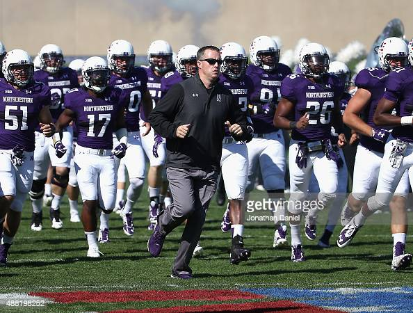 Head coach Pat Fitzgerald of the Northwestern Wildcats runs onto the field with his team before a game against the Eastern Illinois Panthers at Ryan...