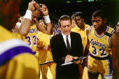 Head Coach Pat Riley of the Los Angeles Lakers draws up a play during a timeout for Magic Johnson and Kareem Abdul Jabbar during an NBA game circa...